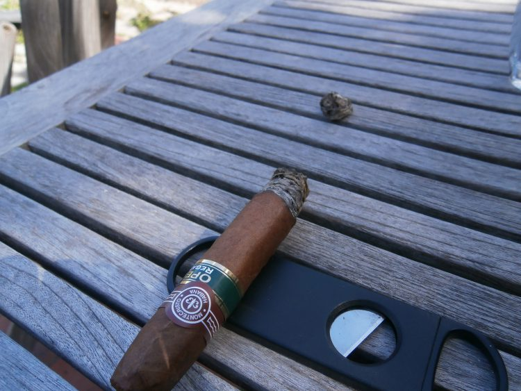 Half a burnt Montecristo Open Regata on a plastic cigar cutter