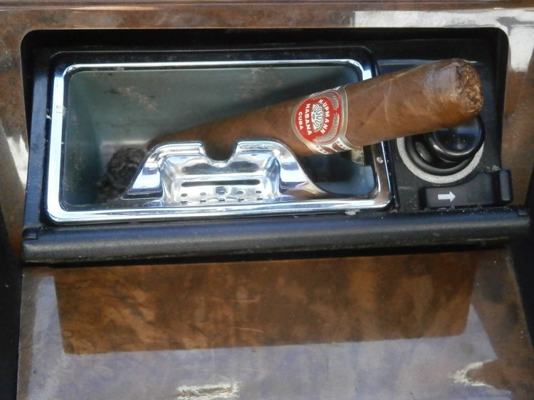 H. Upmann Monarcas, two thirds gone, in a car ashtray