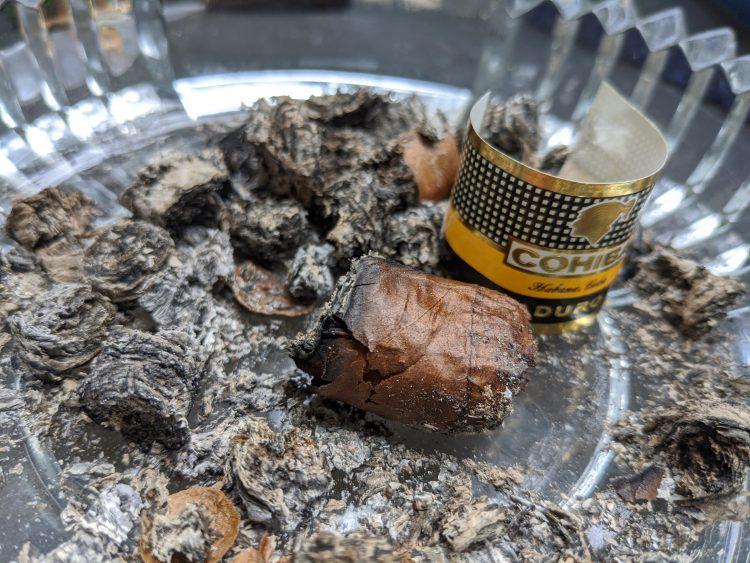Cohiba Mágicos nub, lying amongst its ashes